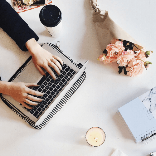 Woman typing on laptop with flowers nearby.