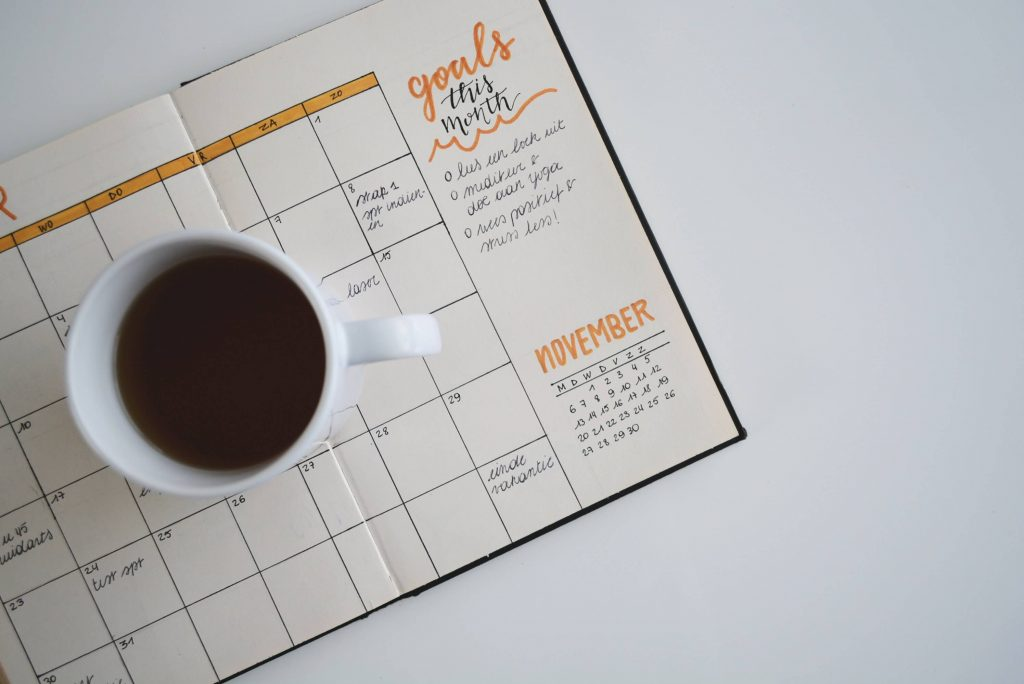 Coffee cup on top of a planning calendar.